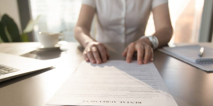 Real estate agent offers client to sign rental agreement, closeup