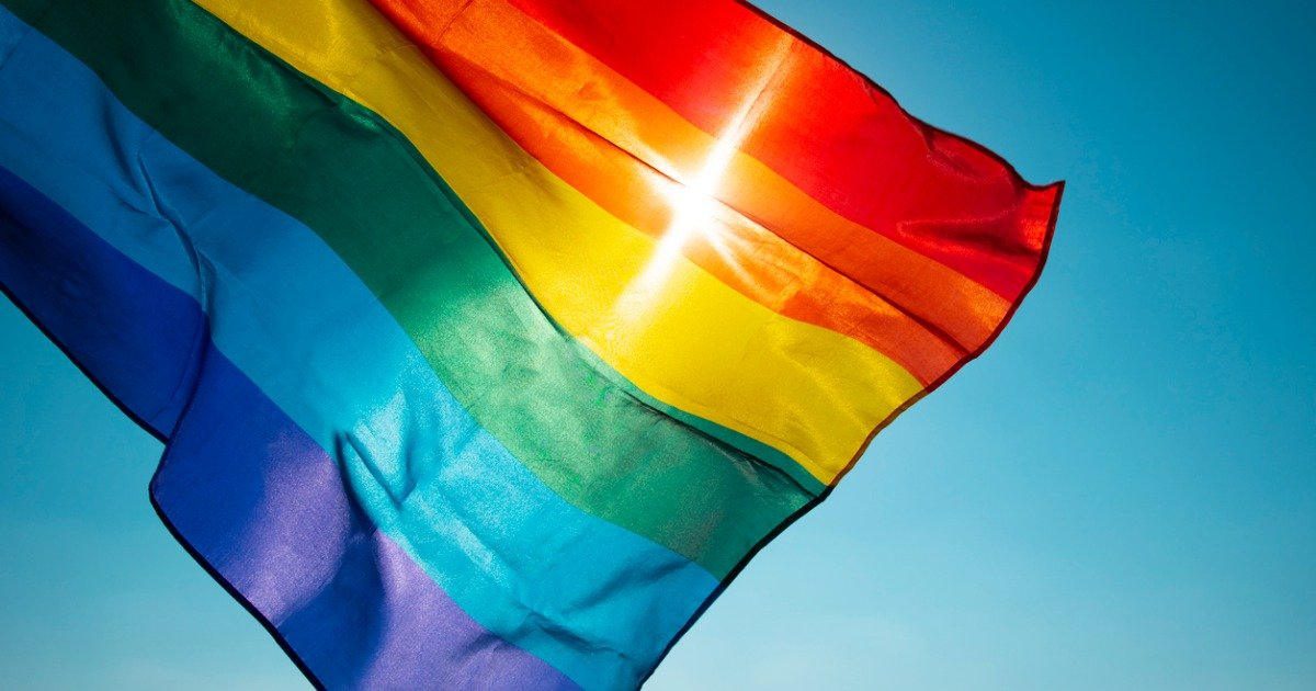 rainbow-flag-waving-on-the-blue-sky-picture-id1157185747