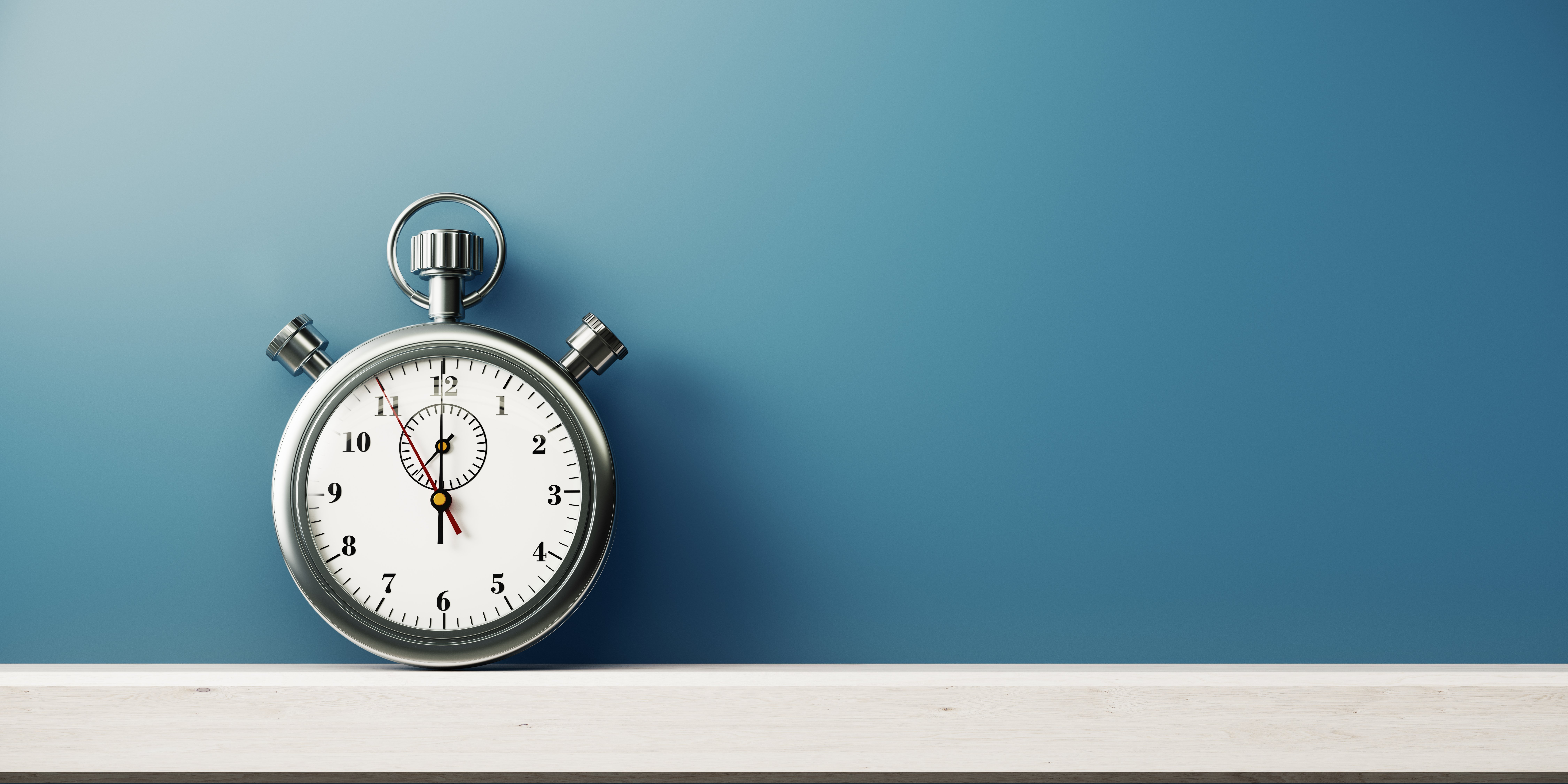 Silver Colored Stopwatch In Front of Blue Wall
