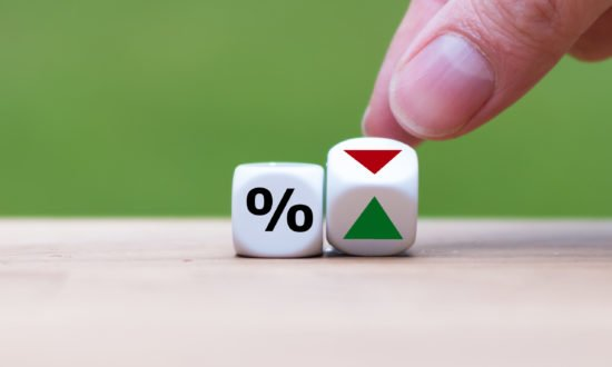 Hand is turning a dice and changes the direction of an arrow symbolizing that the interest rates are going down (or vice versa)