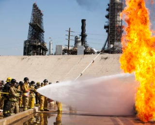 https-www-itpaystobecovered-com-wp-content-uploads-sites-15-2021-05-firemen-putting-out-fire-at-oil-refinery_gettyimages-523312596-320x259-jpg