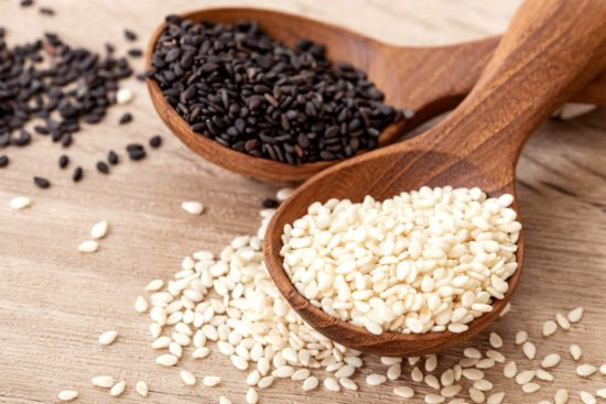 organic Black and white sesame seeds in a wooden spoon , top vie